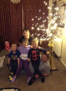 Back at Mums - Alfie, Harvey, Eva and Zak sat on Gav next to Mums new 'Christmas' tree
